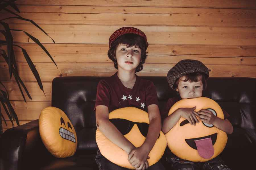 two boys sitting on sofa holding emoji throw pillows